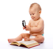 Little child play with book and magnifier Royalty Free Stock Images