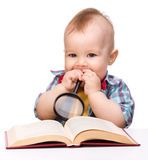 Little child play with book and magnifier Stock Photos