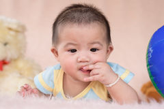 Little child play with her teeth and mouth on soft bed. And toys Royalty Free Stock Photography