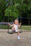 Little child at playground swinging Stock Photo