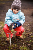Little child playing with dangerous tools. Outdoors Royalty Free Stock Photography