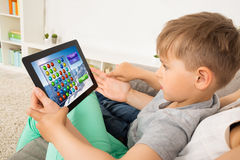 Little Child Playing Game On Digital Tablet. Little Child Sitting On Sofa Playing Game On Digital Tablet Royalty Free Stock Photos