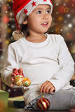 Little child playing happy with Christmas decorations stock images