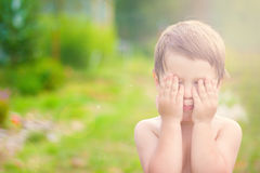 Little child is playing hide-and-seek hiding face in sunlight with boke Stock Photo