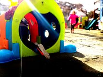 Little child playing and hiding in a colourful toy in a playground, fun and play concept. Hide and seek stock photography
