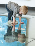 Little child playing with his reflexion on the floor Stock Photography