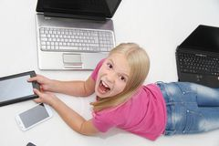 Little child playing at home with tablet, laptop and phone Stock Photography