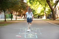 Little child playing hopscotch drawn with colorful chalk. On asphalt stock photos
