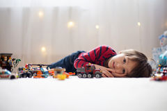 Little child playing with lots of colorful plastic toys indoor Stock Images