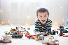 Little child playing with lots of colorful plastic toys indoor Royalty Free Stock Image