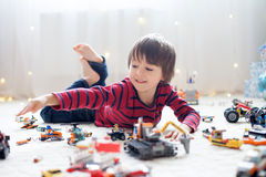 Little child playing with lots of colorful plastic toys indoor. Building different cars and objects Royalty Free Stock Photo