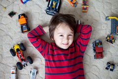 Little child playing with lots of colorful plastic toys indoor Royalty Free Stock Photos