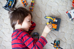 Little child playing with lots of colorful plastic toys indoor Royalty Free Stock Images