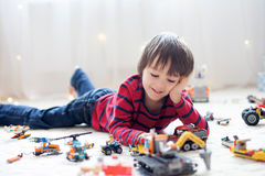 Little child playing with lots of colorful plastic toys indoor Stock Photography
