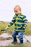 A little child is playing in a muddy puddle. At field stock photography