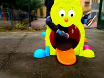 Little child playing otudoor in a playground with a colourful toy, fun and play concept royalty free stock image