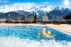 Child in outdoor swimming pool of alpine resort stock image