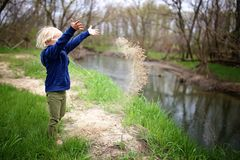 Little Child Playing Outside by the River, Throwing Sand in the Water. A little girl child is playing outside by the river, throwing sand into the water stock photo
