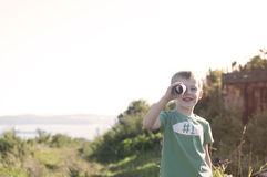 Little child playing pirate, looking at spyglass made from cardb Royalty Free Stock Photo