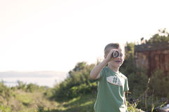 Little child playing pirate, looking at spyglass made from cardb Stock Photo