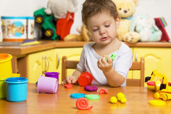 Little child playing plasticine stock photos