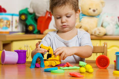 Little child playing plasticine. 2 years old child playing plasticine in children's room Stock Photos