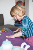 Little child playing with plasticine. Blonde two years old child with striped blue and white sweater inside home playing modeling plasticine on purple table Stock Photos