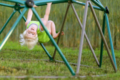 Little Child Playing at PLayground Climbing on Monkey Bars Stock Images
