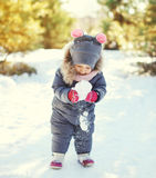 Little child playing with snowball in winter Royalty Free Stock Photo