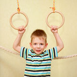 Little child playing sports on gymnastic rings. Little child playing sports at sport center. Kid exercising on gymnastic rings Royalty Free Stock Photo