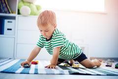 Little child playing with toy cars. Boy sitting on the floor at home Stock Images