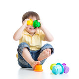 Little child is playing with toys while sitting on floor, isolated over white Stock Photography
