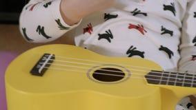 Little child playing ukulele on sofa. 4K Video : Little child playing ukulele on sofa stock video footage