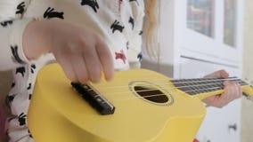 Little child playing ukulele on sofa. 4K Video: little child playing ukulele on sofa stock footage