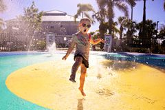 Little Child Playing in Water at Splash Park on Summer Day stock image