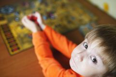 Little child plays board game Stock Images