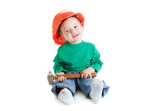 Little child plays with hammer and orange construction protective helmet  on white background. Stock Photos