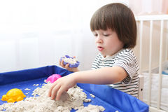 Little child plays kinetic sand at home Royalty Free Stock Image