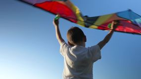 Little child plays with kite on blue sky background. concept of dream flight. Little child plays with a kite on blue sky background. concept of dream flight stock video footage