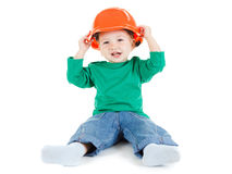 Little child plays with orange construction protective helmet  on white background. Royalty Free Stock Photography