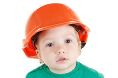 Little child plays with orange construction protective helmet  on white background. Stock Photos