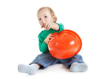 Little child plays with orange construction protective helmet  on white background. Stock Images