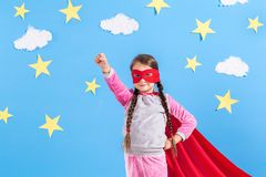 Little child plays superhero. Kid on the background of bright blue wall. Stock Photo