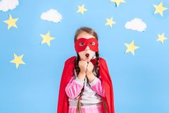 Little child plays superhero. Kid on the background of bright blue wall with white clouds and stars . Girl power concept. Red, pink and blue colors royalty free stock photos