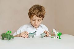 A little child plays with toys animals Royalty Free Stock Image