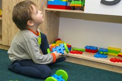 Little child plays with toys in kindergarten. Little boy playing in the children room stock photos