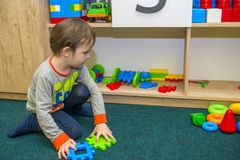 Little child plays with toys in kindergarten. Little kid playing in the children room royalty free stock image