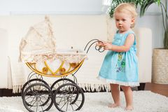 Little child is posing with small vintage pram Royalty Free Stock Photo