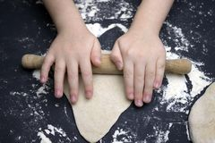 Little child preparing dough for backing. Kid`s hands, some flour, wheat dough and rolling-pin on the black table. Children hands. Making the rye dough for Royalty Free Stock Photo