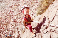 Little Child in protective Helmet climbing Rock Stock Photos
